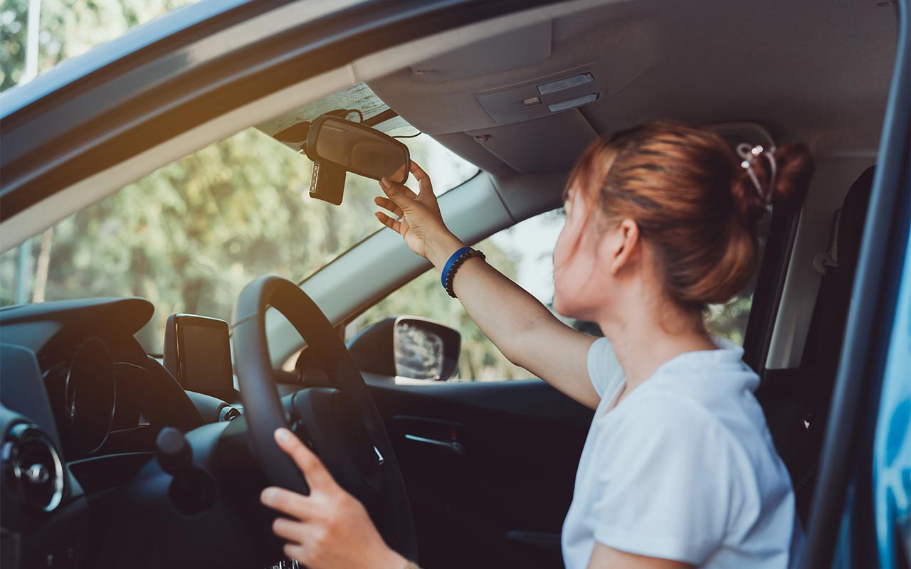 teen driver in car checking rearview mirror