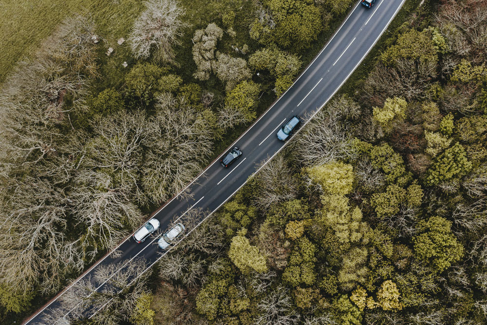 Aerial view of two lane highway lined by trees.