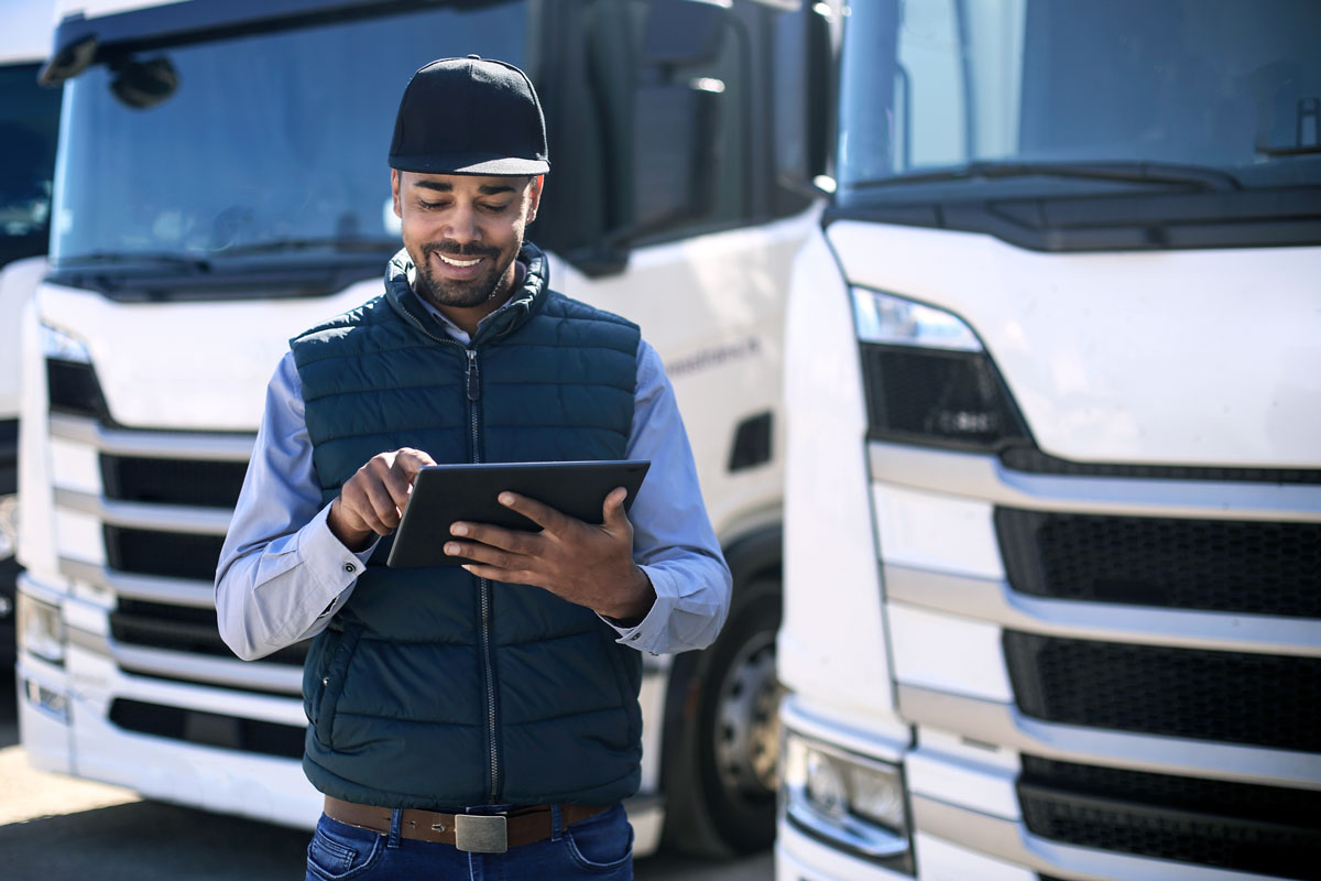A business man works on an iPad, standing in front of his fleet of vehicles.