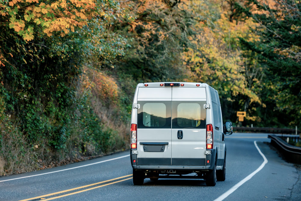 Delivery van driving down a highway lined by fall foliage.