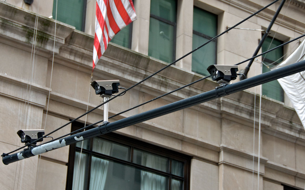 Three license plate scanner devices mounted to pole.