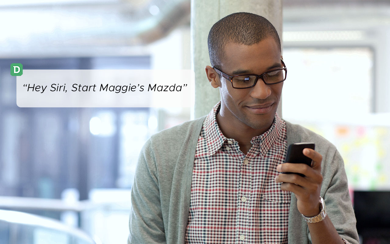"Man stands smiling down at his phone. ""Hey Siri, start Maggie's Mazda"" to the left."