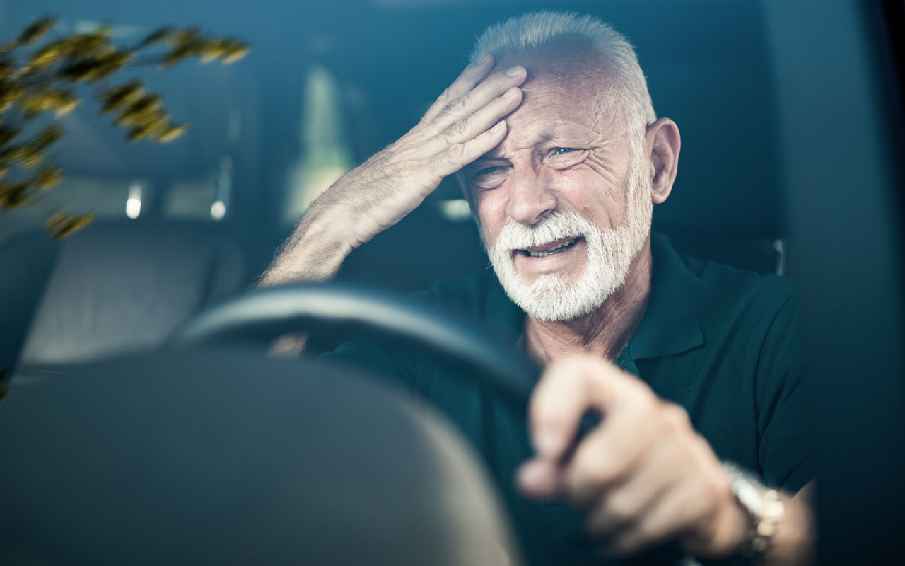 An elderly man behind the wheel of a vehicle appears distressed as he touches his forehead.